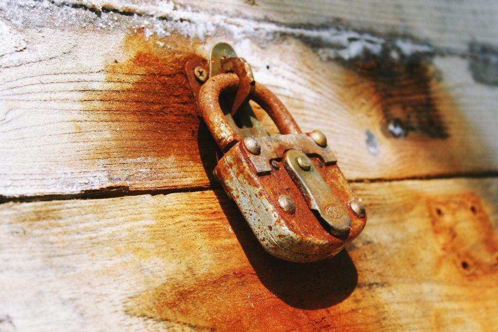 rusty padlock on wood signifying the Latch Key Life