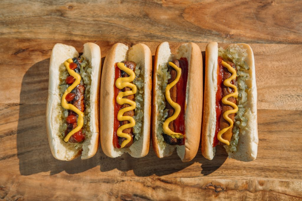 four hot dogs with toppings