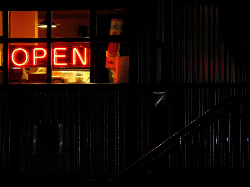 neon open sign in a dive bar window